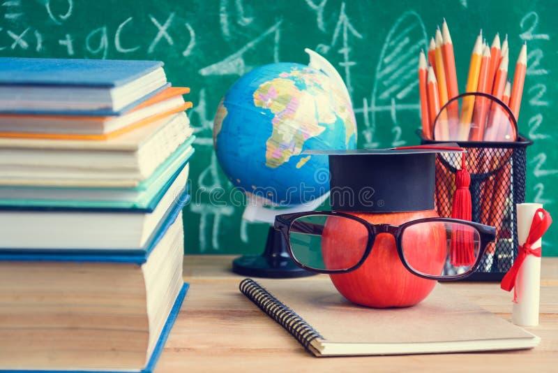 Apple-Wissens-Symbol und Bleistift-Bücher auf dem Schreibtisch mit Brett b lizenzfreies stockfoto