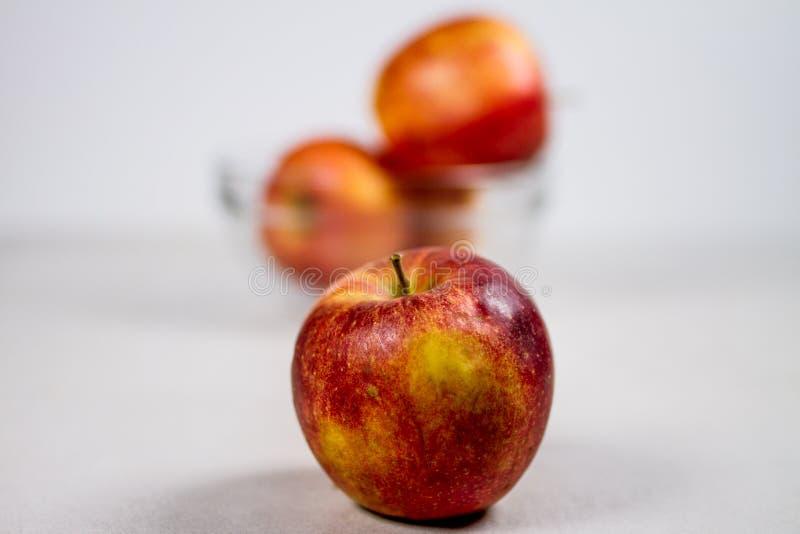 Apple y bol de vidrio jugosos rojos con las manzanas aisladas en el fondo blanco imagenes de archivo