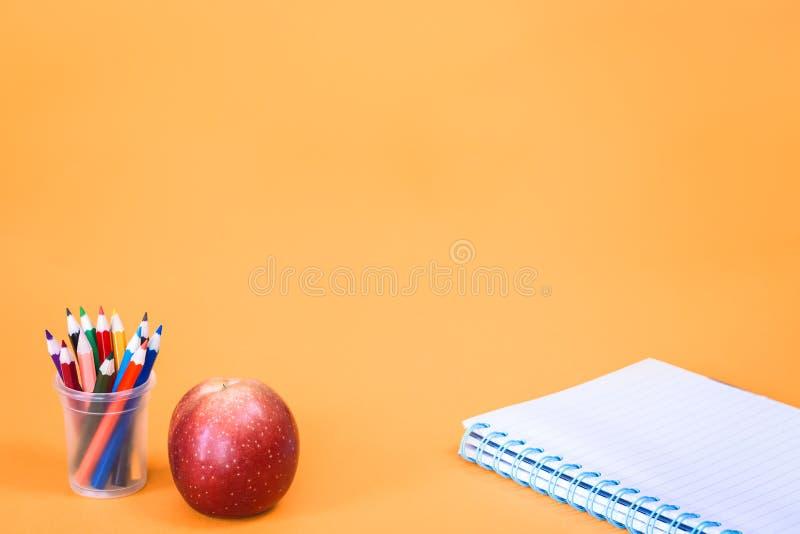 Apple z o??wkami i notatnikiem na pomara?czowym tle zdjęcie stock