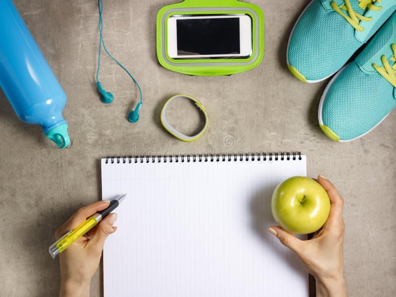 Apple, zapatillas de deporte, perseguidor y escritura femenina de la mano en cuaderno imagenes de archivo