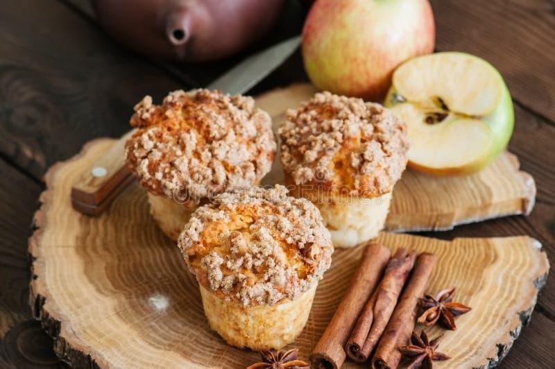 Apple-Zimtkrümelmuffins, -gewürze und -hälfte von Äpfeln auf einem w lizenzfreie stockfotografie