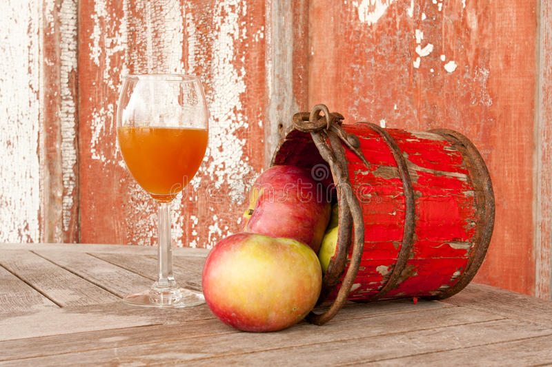Apples and Apple Cider. Apples falling out of a bucket next to a glass of apple cider stock image