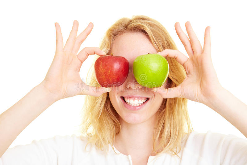 Apples as eyes. Happy woman holding two apples in front of her eyes stock photography