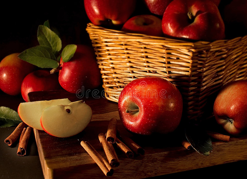 Apples with cinnamon sticks. On a wood table royalty free stock photography