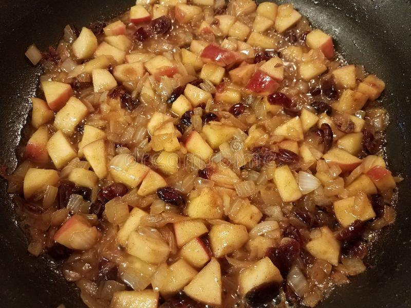Apples and cranberries and sauce cooking in a frying pan stock images