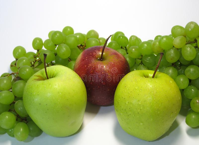 Apples and grapes - beauty and benefit, taste and health, an inexhaustible source of vitamins. royalty free stock image