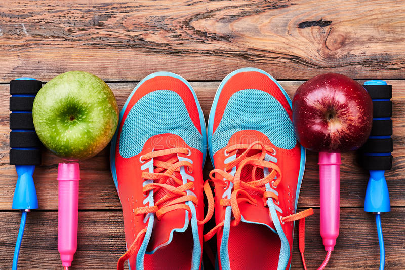 Apples, gumshoes and jump rope. Invitation to a sport gym royalty free stock photography