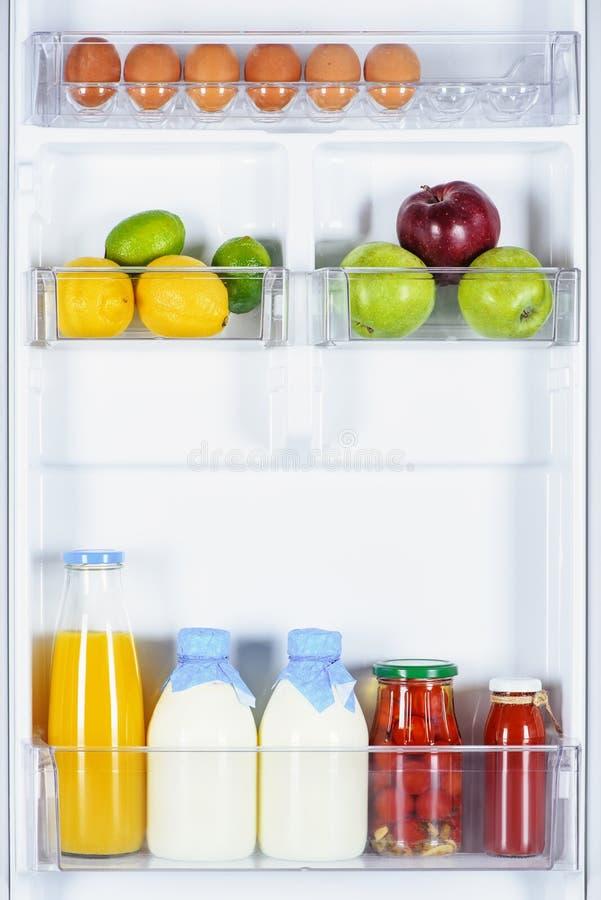 Apples lemons juice and milk. In fridge royalty free stock photography