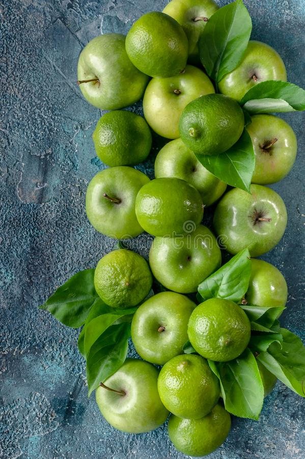 Apples and limes on a dark blue concrete background. Top view. Vertical shot stock photo