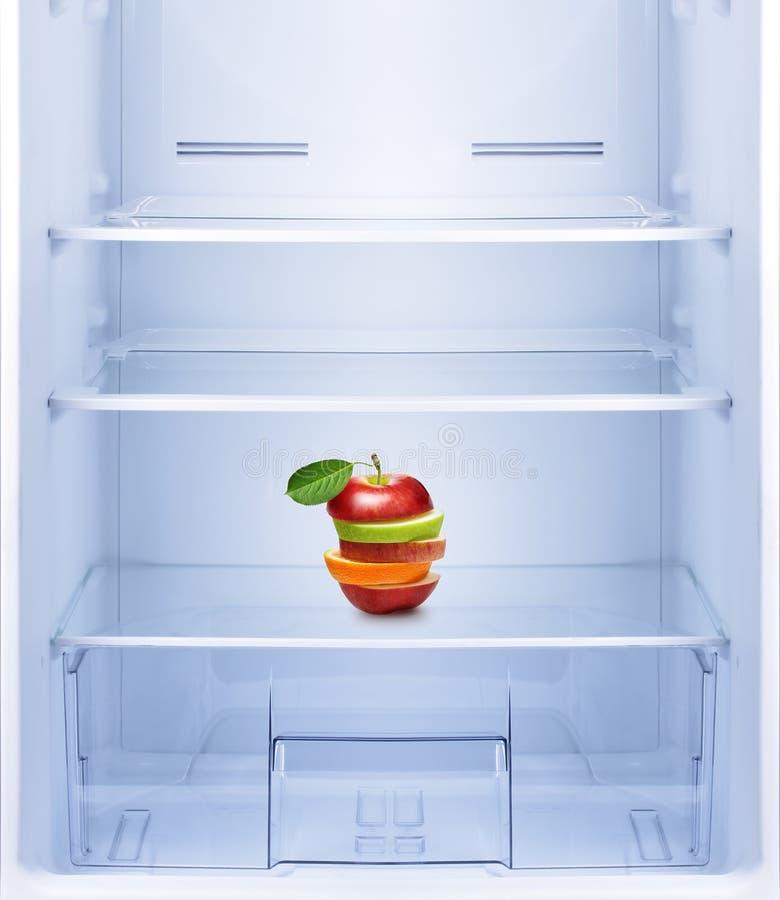 Apples and orange fruit in empty refrigerator. stock photo