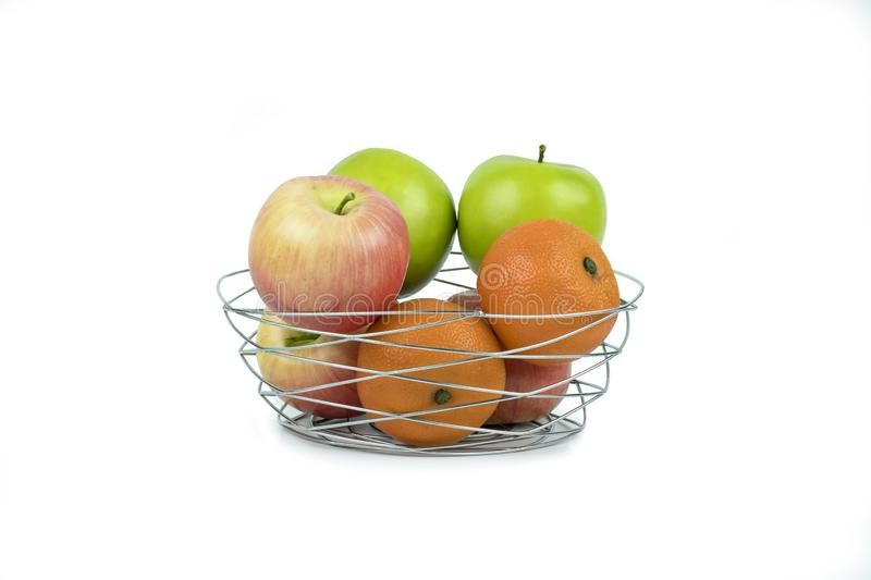 Apples and oranges in a decoratively wire basket put on isolated white background with clipping path. Apples and oranges in a decoratively wire basket put on stock photo