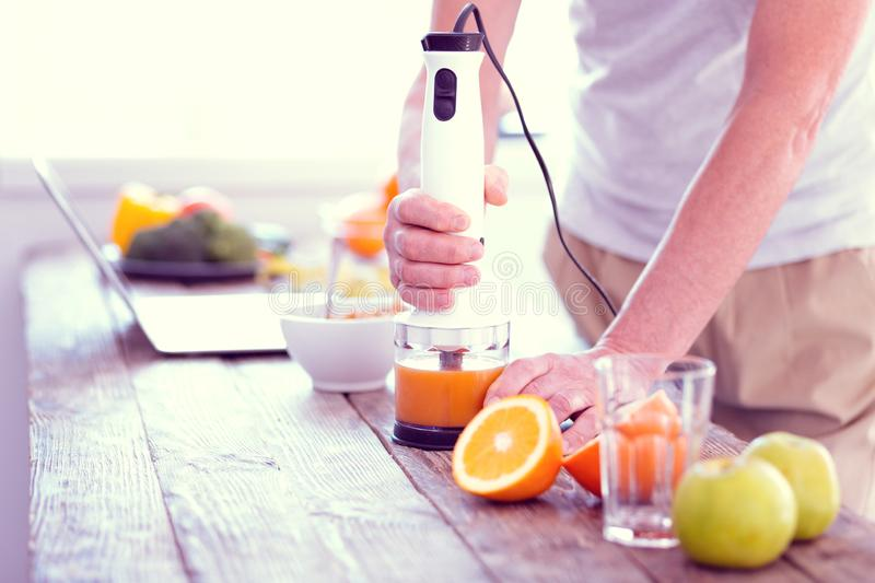Man standing near the table while blending oranges and apples for juice. Apples and oranges. Man wearing beige trousers standing near the table while blending royalty free stock image