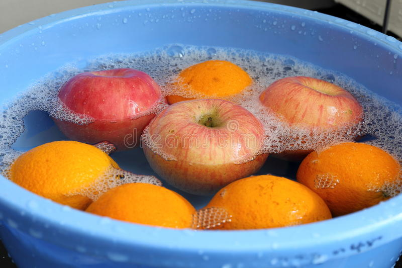Apples and Oranges in Water. Apples and oranges being washed in a blue container stock photos