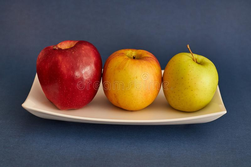 Beautiful apples of three colors. Apples in order in three colors, green, yellow and reddish stock photos