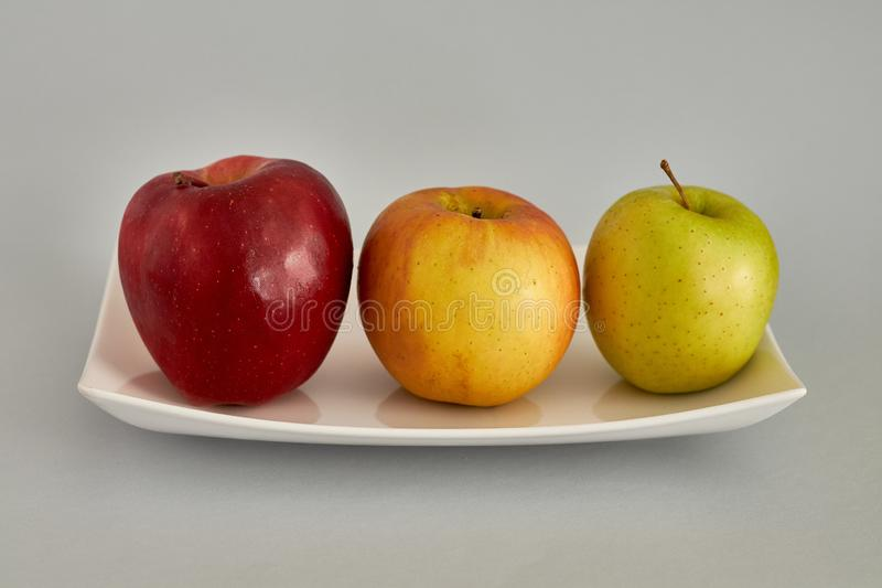 Beautiful apples of three colors. Apples in order in three colors, green, yellow and reddish royalty free stock photo