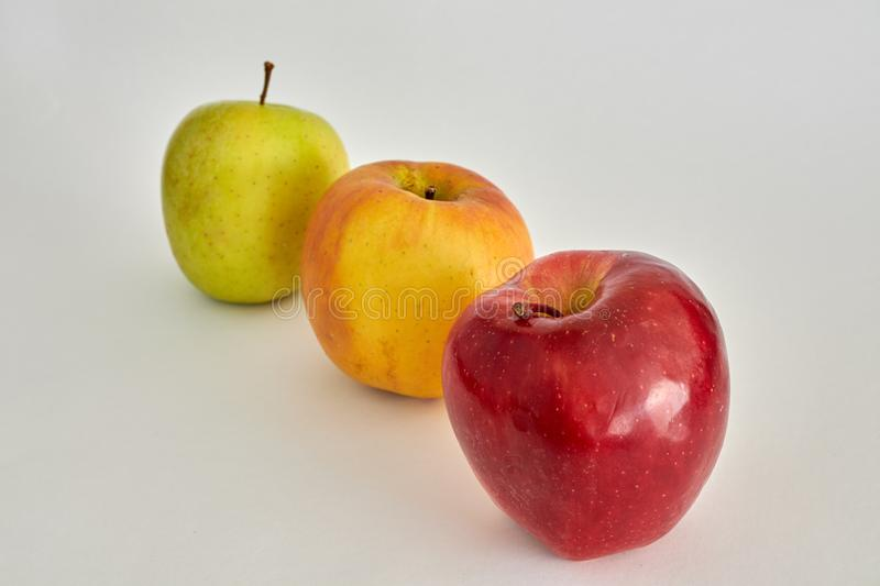 Beautiful apples of three colors. Apples in order in three colors, green, yellow and reddish royalty free stock images