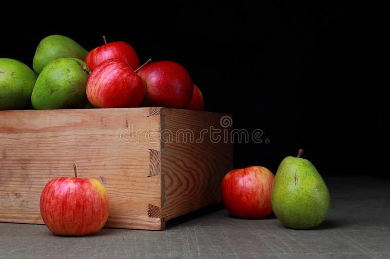Apples and pears. Juicy fruits in old wooden box. Red apples and green pears stock photography