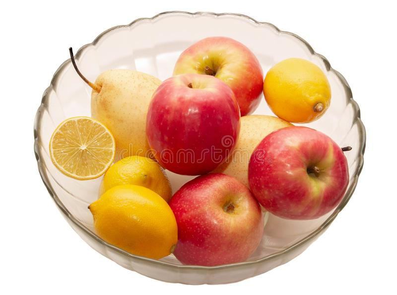 Apples, pears, lemons in a transparent glass plate on a light background royalty free stock photos