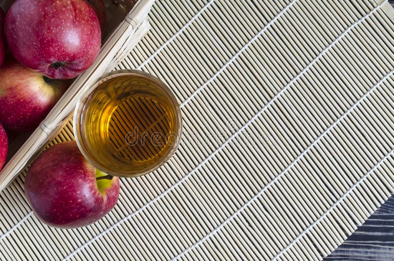 Apples red Apple juice in a transparent glass on a natural background. Basket of apples stock image