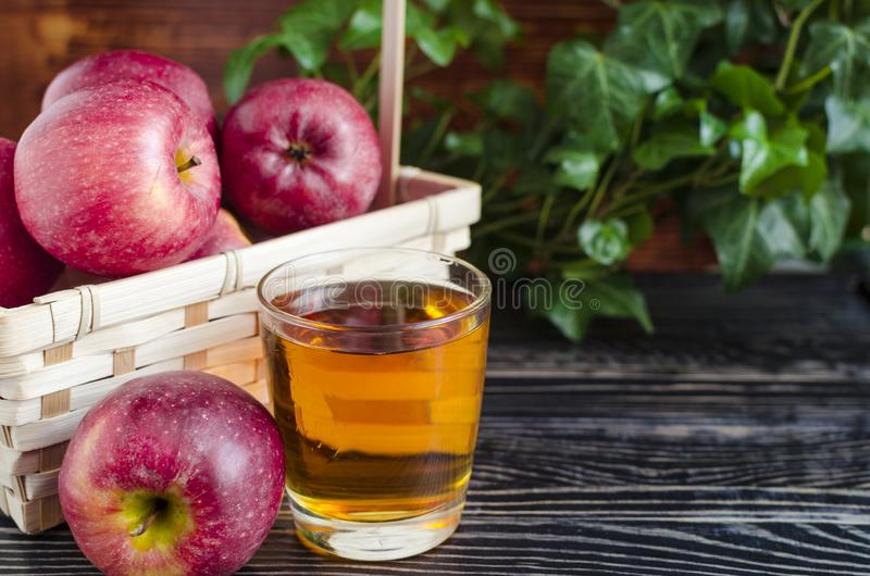 Apples red Apple juice in a transparent glass on a natural background. Basket of apples stock images