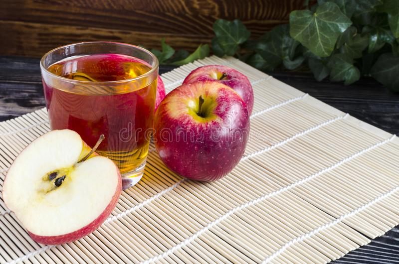 Apples red Apple juice in a transparent glass on a natural background. Basket of apples royalty free stock images