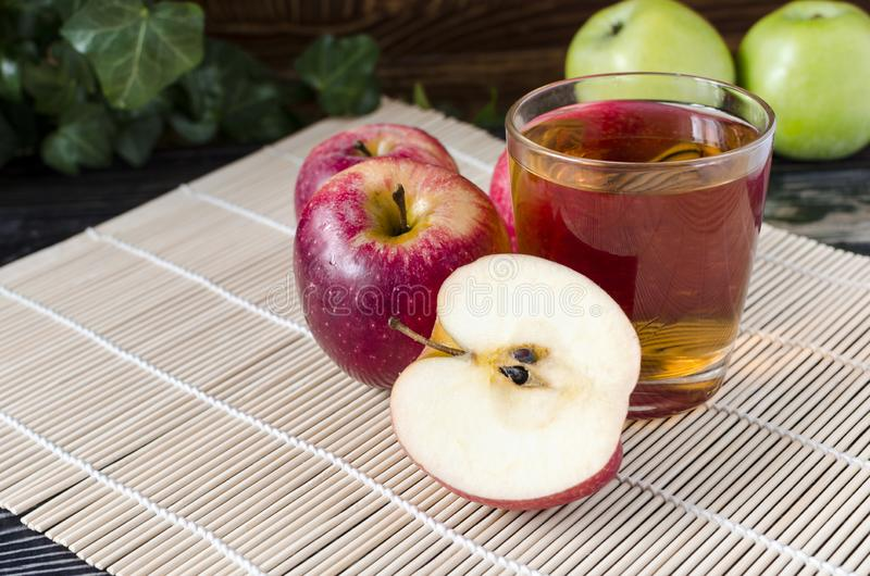 Apples red and green Apple juice in a transparent glass on a natural background. Apples red Apple juice in a transparent glass on a natural background basket of stock image