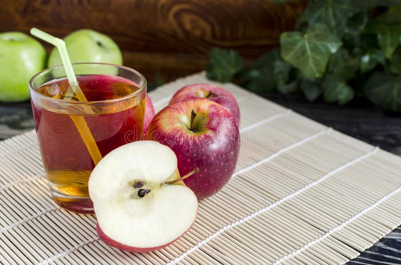 Apples red and green Apple juice in a transparent glass on a natural background. Apples red Apple juice in a transparent glass on a natural background basket of royalty free stock photos
