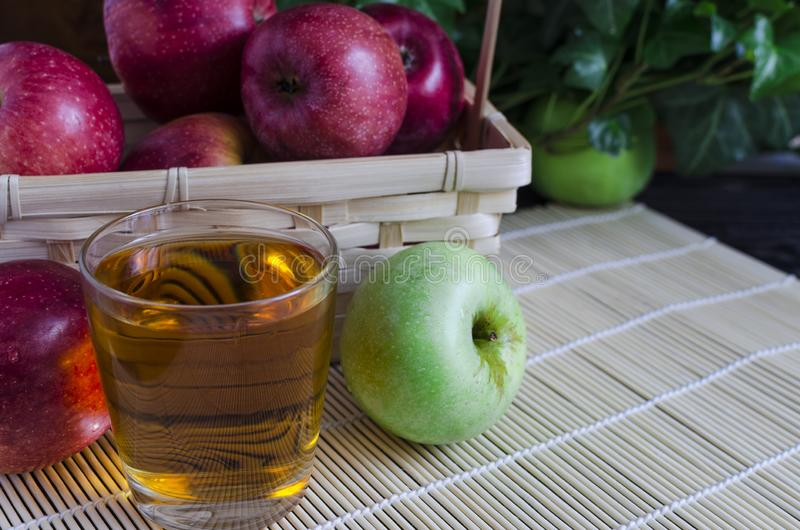 Apples red and green Apple juice in a transparent glass on a natural background. Apples red Apple juice in a transparent glass on a natural background basket of stock photo