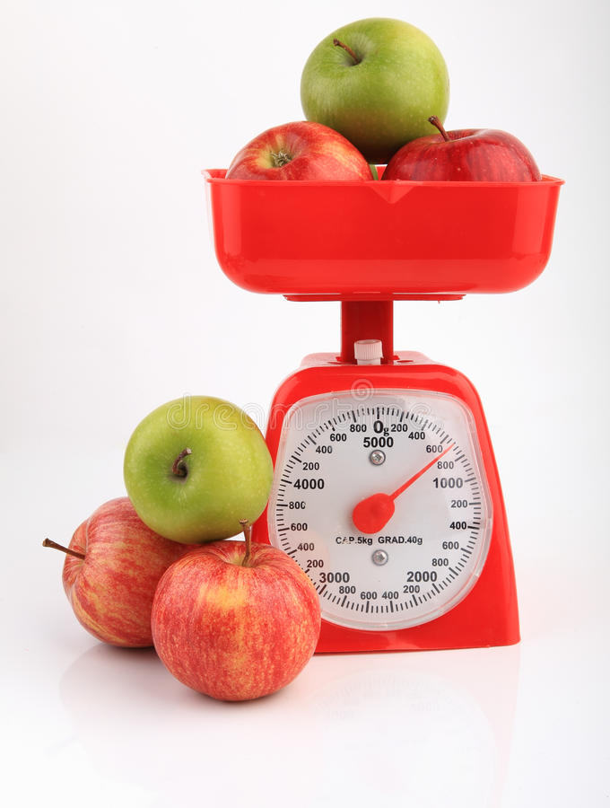 Apples on red weighing scale. Red and green apples on weighing scale over white background royalty free stock photography