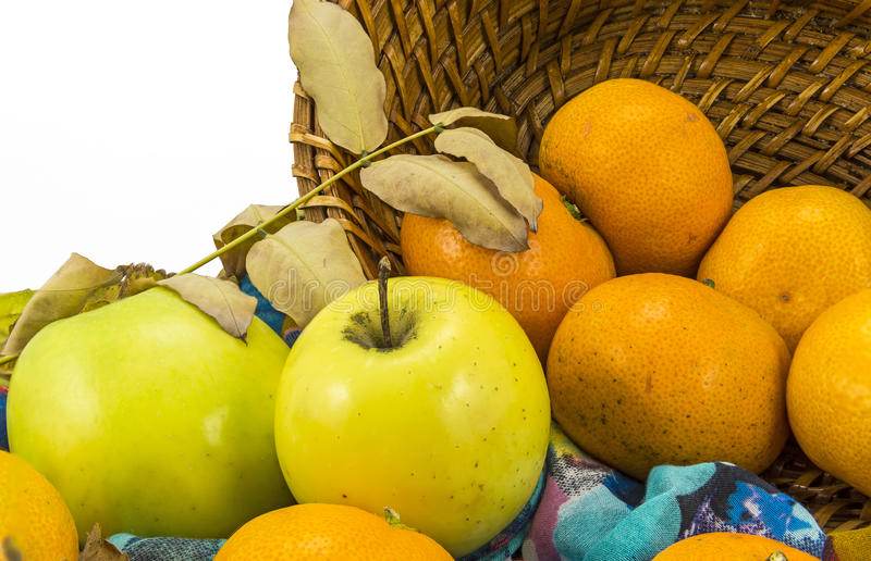 Apples, tangerines and a wicker basket on a white background royalty free stock photos
