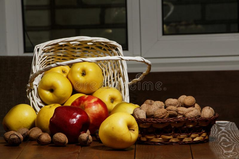 Apples with walnuts in a white basket on a wooden table. Close-up. Apples and walnuts on the table. royalty free stock image
