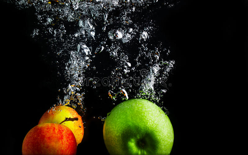 Apples in water. Apples falling into the water with a splash and air bubbles. Healthy food on black background. Wash fruits royalty free stock photography