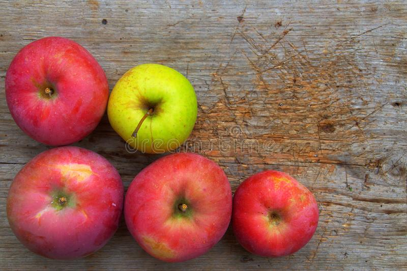 Apples On Wood Background. Green apple between four red home grown apples on old grungy wooden plank stock photo