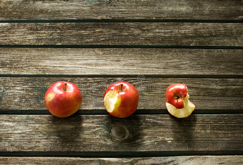 Apples on wooden background. Three red apples on old wooden background royalty free stock photos