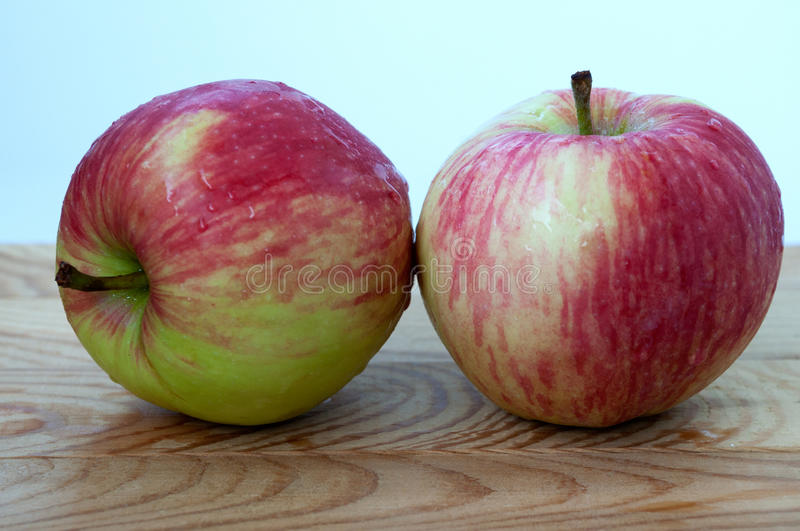 Apples on a wooden surface. Two apples on a wooden surface stock photos
