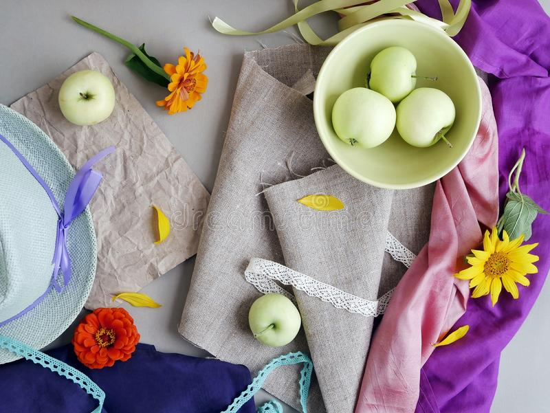 Seasonal decorative composition, still life. Summer, autumn. Apples, yellow petals, green hat and fresh flowers on a light background of gray canvas and pink and royalty free stock images