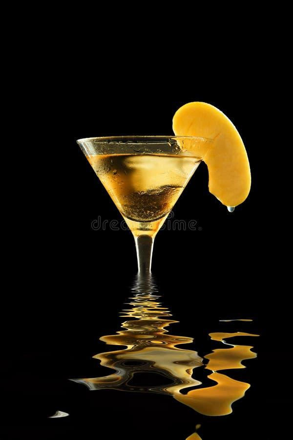 Appletini i ett svettigt coctailexponeringsglas med smältande is som garneras med äppleskivan med hängande waterdrop, reflekterad arkivfoto