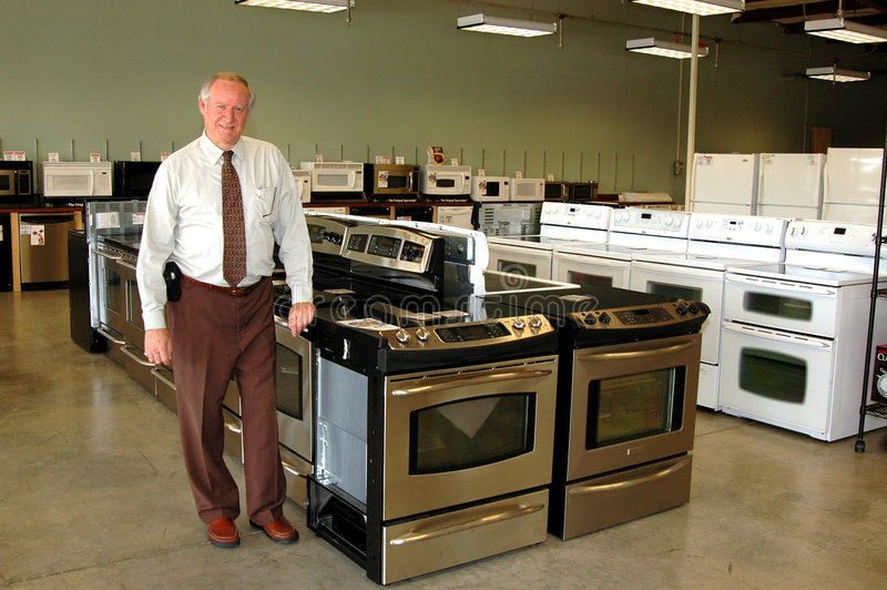 Appliance salesman. A sales man in an appliance store with a range display