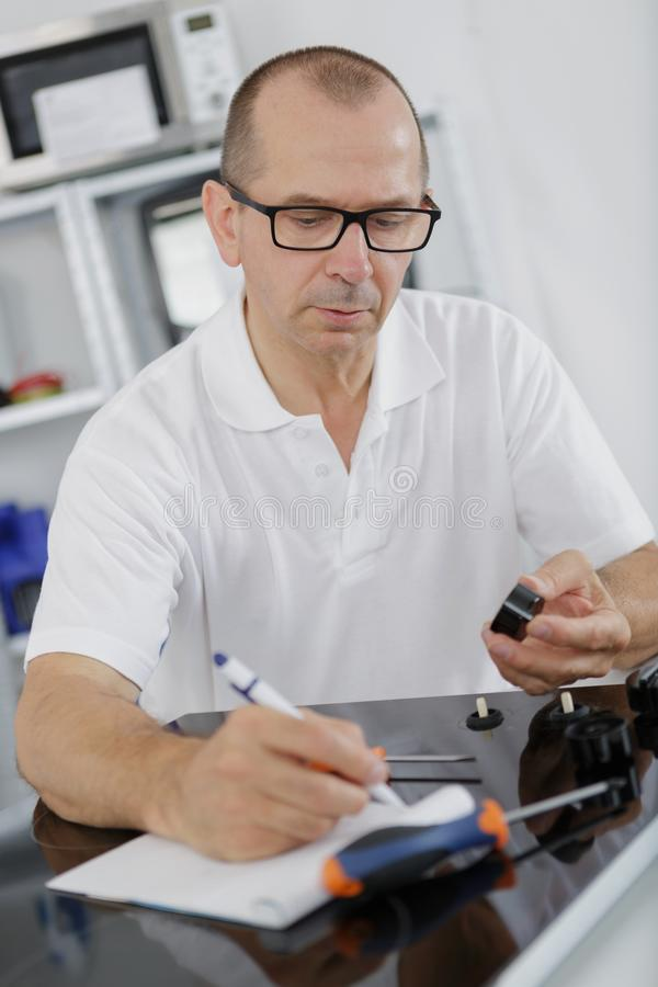 Appliance technician writing notes royalty free stock photo
