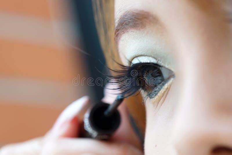 Applicando eye-liner liquido con la spazzola, fine su immagini stock