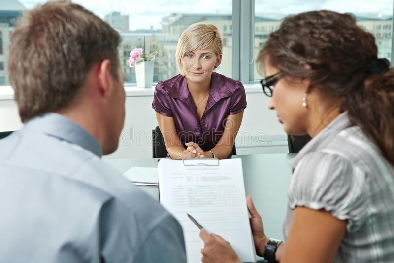 Applicant during job interview. Attractive woman applicant hoping in good resuts after job interview. Over the shoulder view stock photography