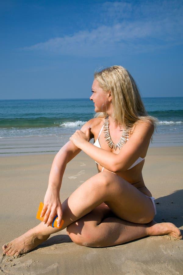 application de la femme de bronzage de lotion photos stock