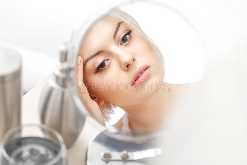 Application de maquillage. Belle femme regardant son visage dans le Mirro image libre de droits