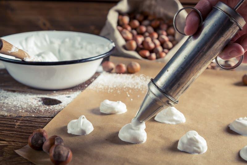 Application des meringues sur le papier de cuisson pour des macarons image stock