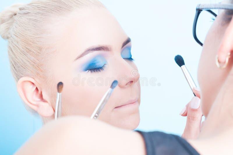 Application du maquillage coloré par professionnel sur la belle fille photo stock