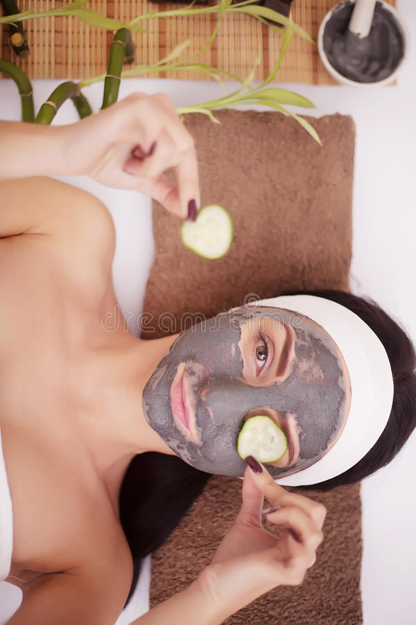 Application du masque facial au visage de femme au salon de beauté image stock
