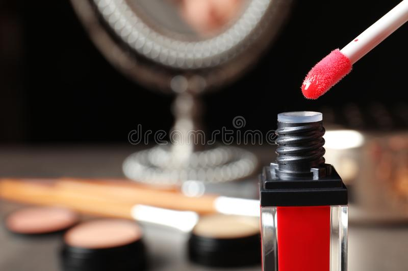 Applicator above liquid lipstick tube on blurred background. Space for text royalty free stock photography