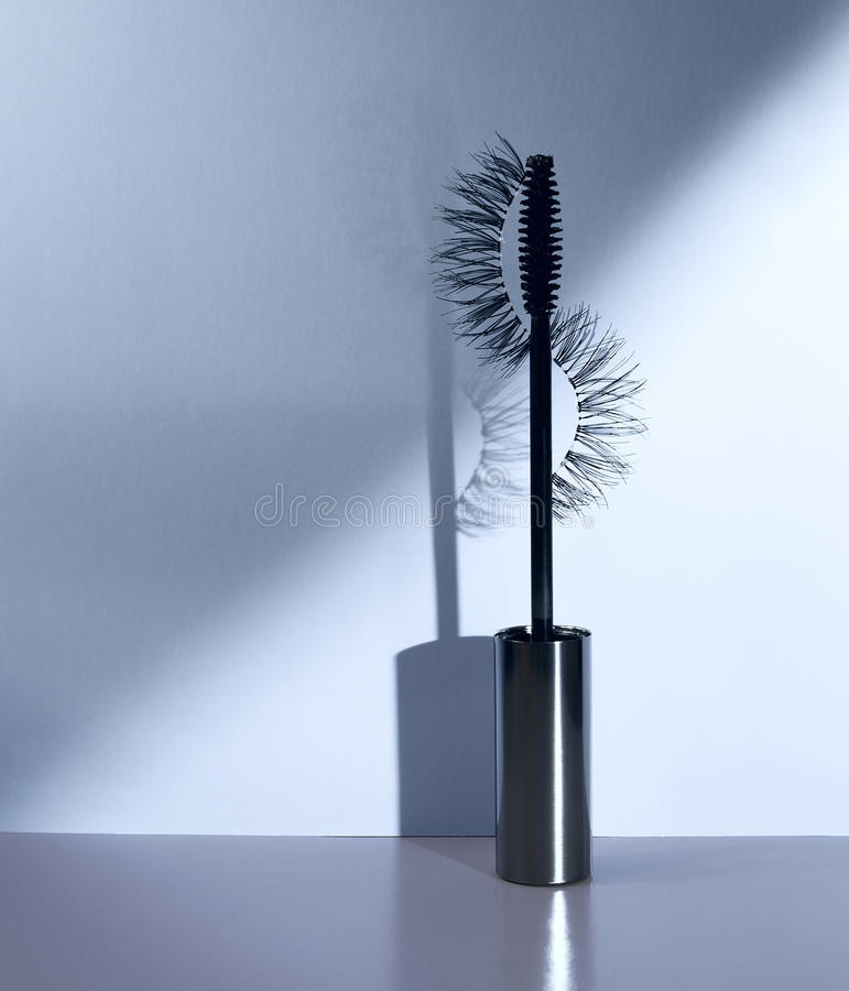 Applicator mascara and false eyelashes with drop shadow on blue background. royalty free stock photo