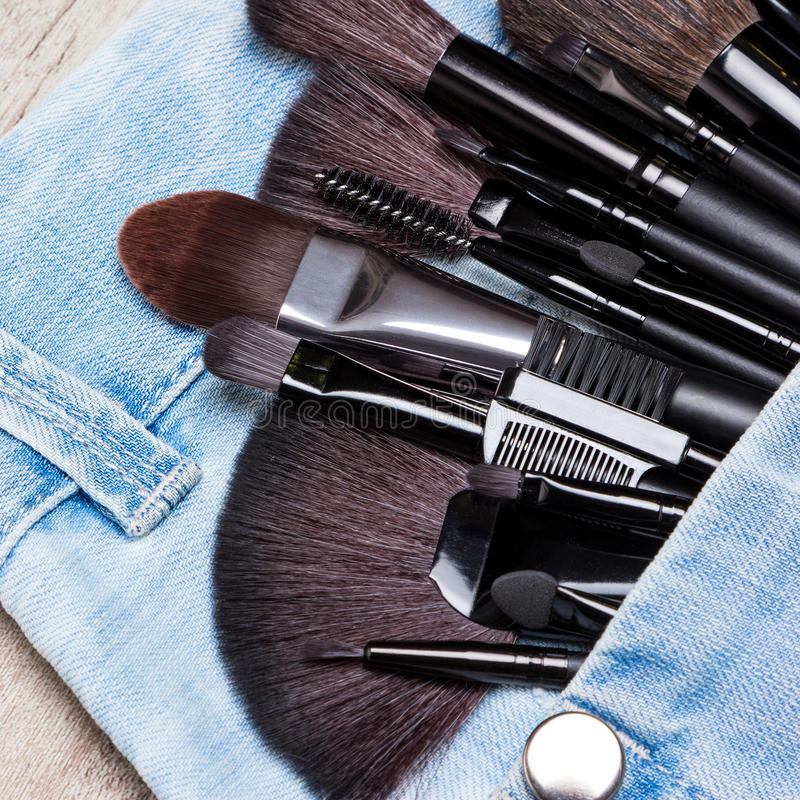 Applicators and makeup brushes in jeans pocket. Professional tools of make-up artist in blue jeans pocket. Sponge tip applicators and makeup brushes: for royalty free stock image