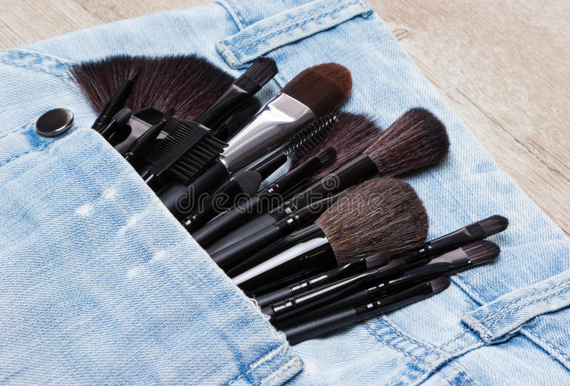 Applicators and makeup brushes in jeans pocket. Professional tools of make-up artist in shabby jeans pocket. Sponge tip applicators and makeup brushes: for stock photography